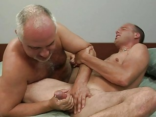 mature homosexual gives younger hunk a handjob on